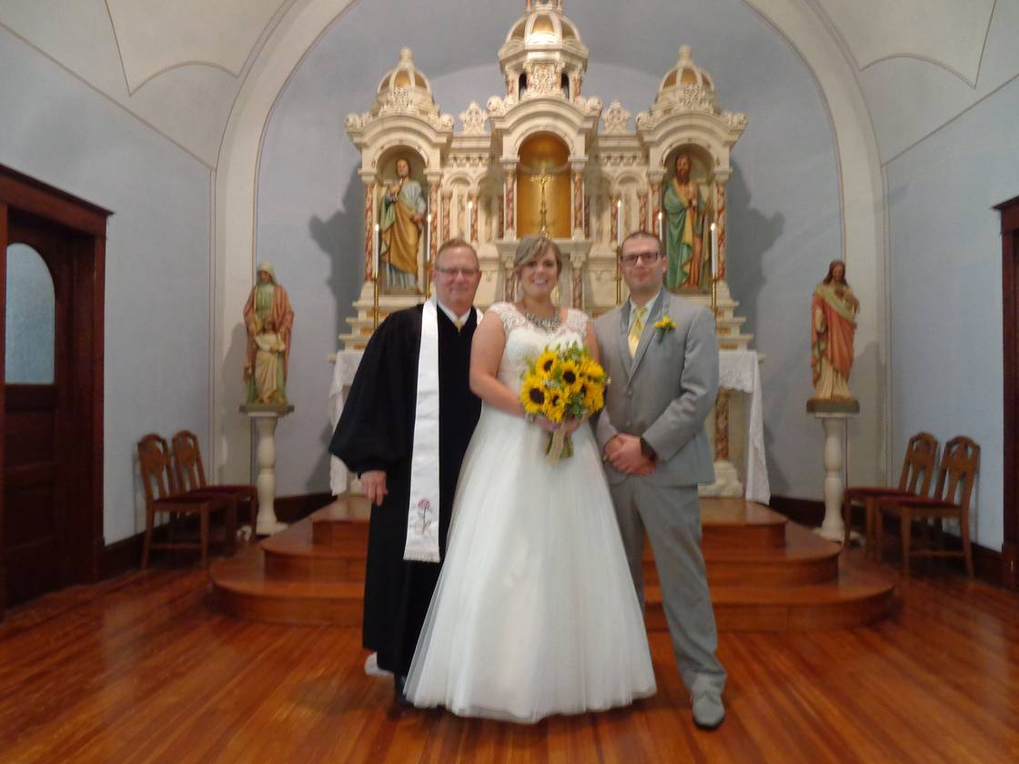 photo of officiant, bride and groom