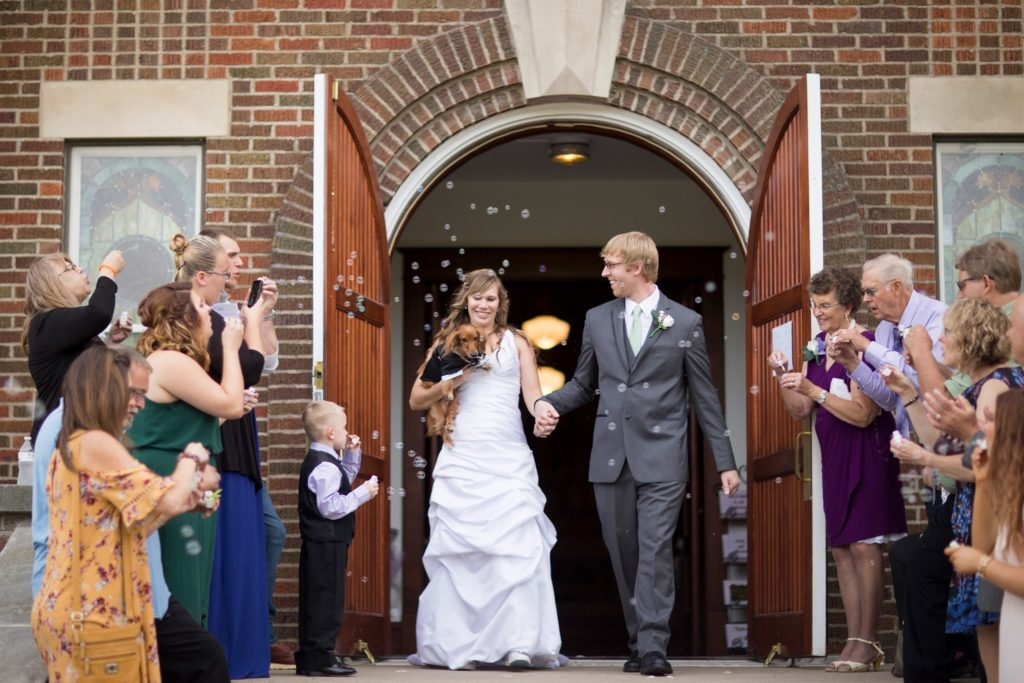Newly married bride and groom leave the Chapel to be greeted by friends and family